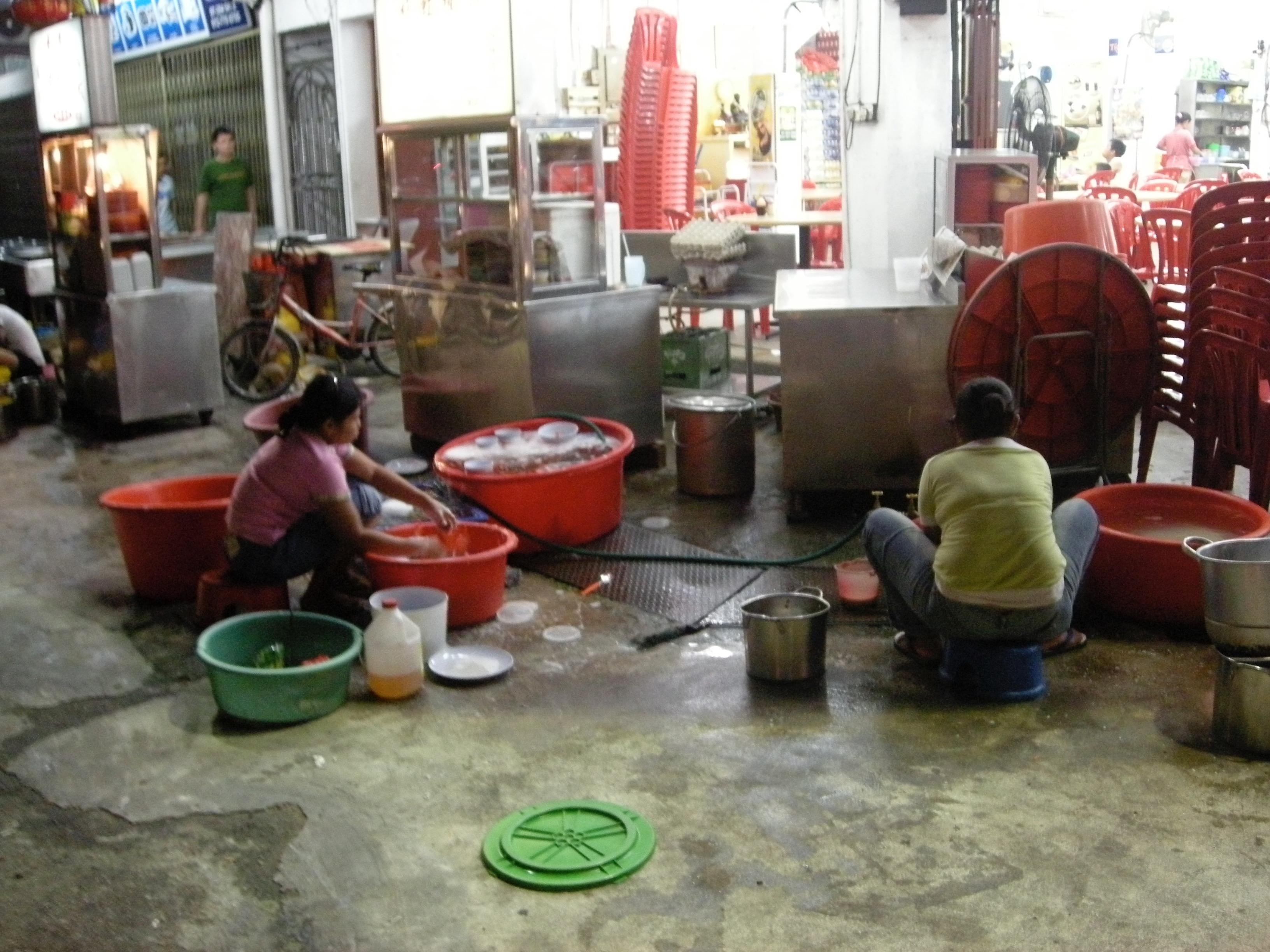 屋台で洗い場で働く人