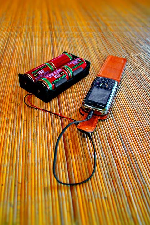 乾電池で携帯の充電をするボルネオ島の人