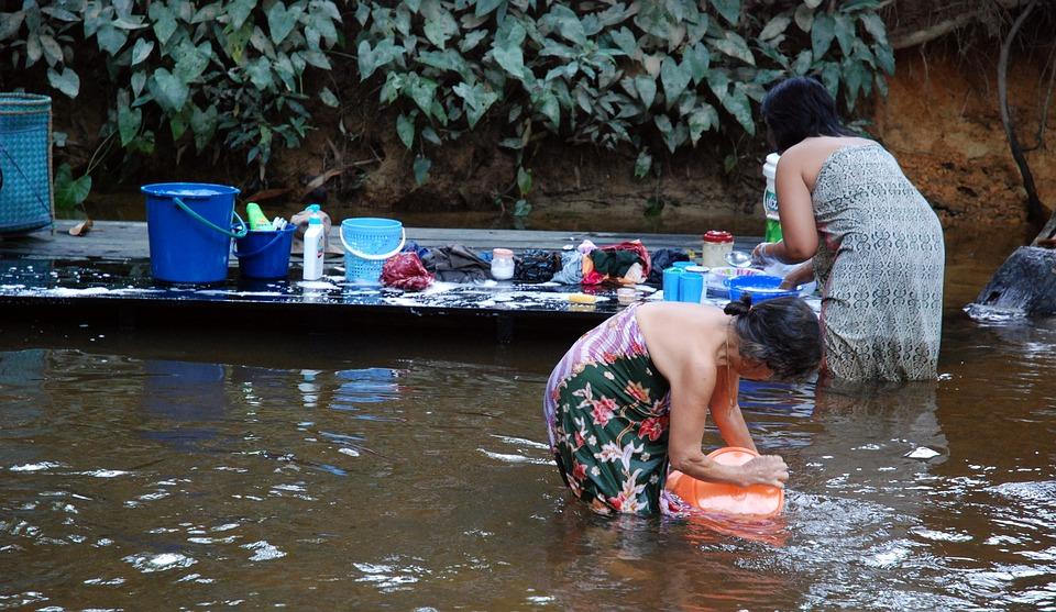 サラワク州の川で洗濯する女性